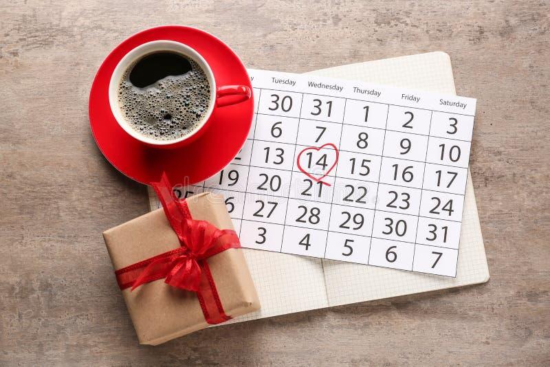 Caixa de presente para o dia de Valentim com xícara de café e calendário na tabela fotos de stock