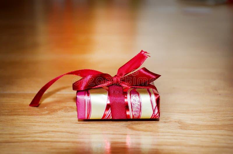 Caixa de presente pequena com fita vermelha em um fundo de madeira imagens de stock royalty free