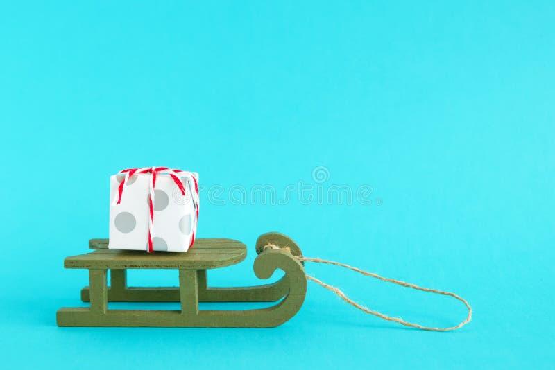 Caixa de presente pequena envolvida do papel branco e cinzento com fita vermelho-branca em um trenó de madeira verde em um fundo  imagem de stock royalty free