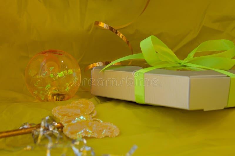 A caixa de presente de prata amarrou a curva amarela da fita no fundo amarelo imagem de stock