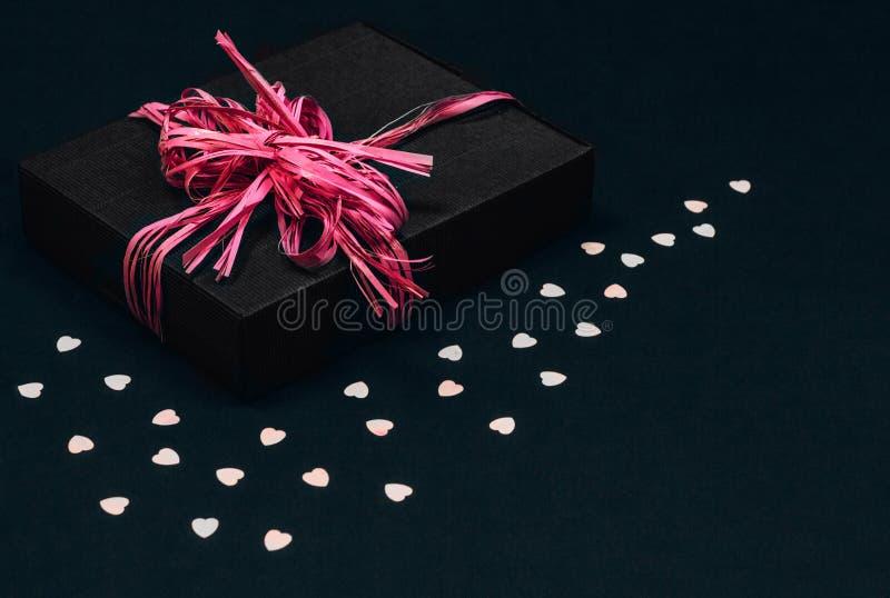 A caixa de presente preta com curva cor-de-rosa da fita no fundo preto polvilhado com o coração deu forma a confetes Copie o espa imagem de stock royalty free