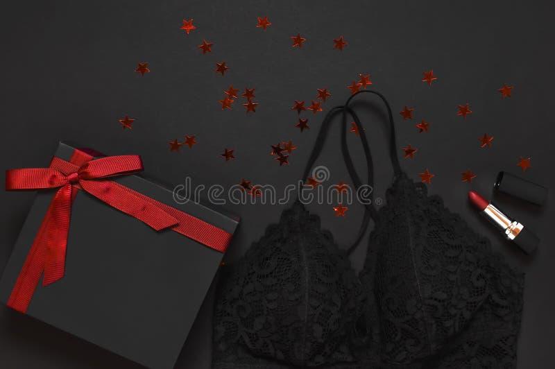 Caixa de presente preta com fita vermelha, roupa interior do sutiã do laço, batom vermelho, confete holográfico na configuração l imagens de stock royalty free