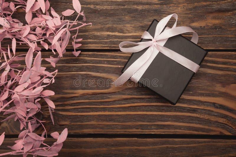 A caixa de presente preta com uma curva está na árvore, e em flores próximas fotografia de stock royalty free