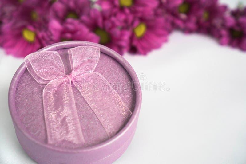 Caixa de presente roxa da forma redonda com curva cor-de-rosa no fundo branco e flores magentas atrás da caixa de presente Para o