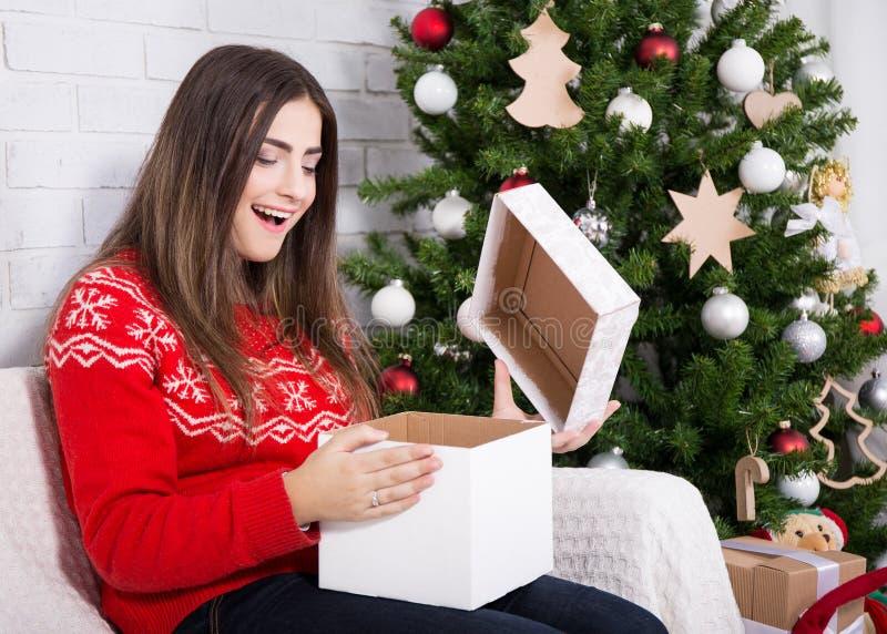 A caixa de presente surpreendida da abertura da mulher próximo decorou a árvore de Natal foto de stock