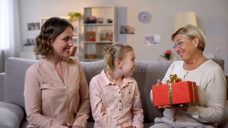 Caixa de presente surpreendida da terra arrendada da avó da filha e da neta, feriado imagem de stock royalty free