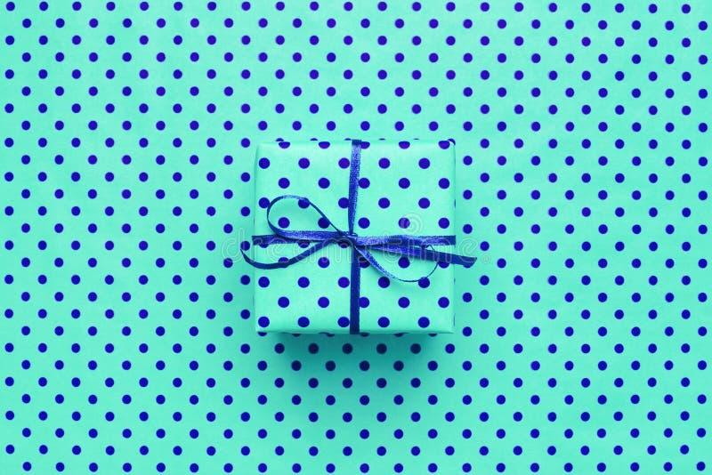 Caixa de presente de turquesa no fundo azul com às bolinhas fotografia de stock