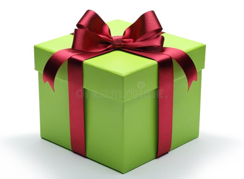 Caixa de presente verde com curva vermelha da fita fotografia de stock royalty free