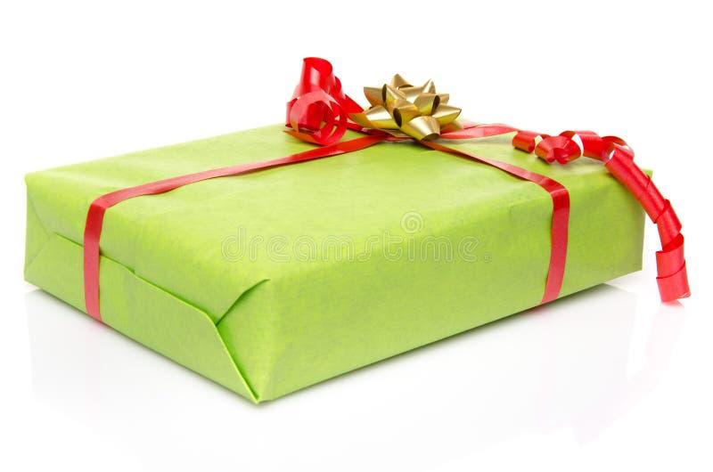 Caixa de presente verde com uma fita vermelha e uma curva dourada fotos de stock royalty free