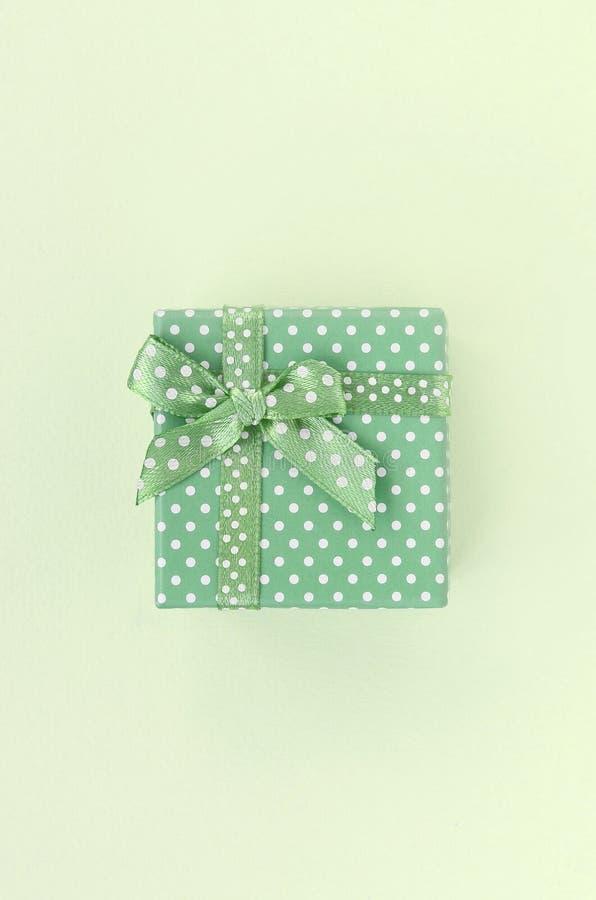 Caixa de presente verde pequena com mentiras da fita em um fundo do cal imagens de stock