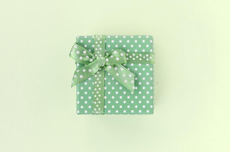 Caixa de presente verde pequena com mentiras da fita em um fundo do cal imagem de stock