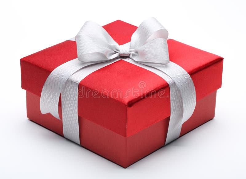 Caixa de presente vermelha com curva branca de prata da fita fotografia de stock royalty free