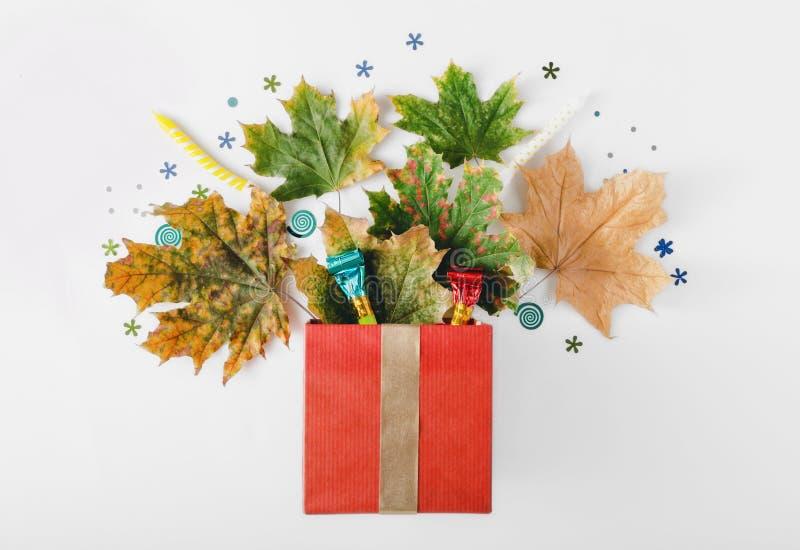 Caixa de presente vermelha com folhas de outono, confetes do partido e noisemakers imagem de stock
