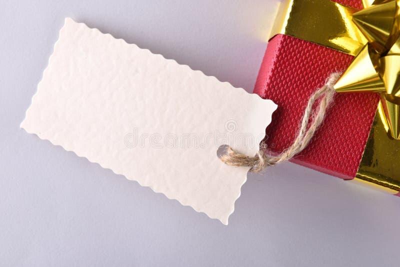 Caixa de presente vermelha com o ascendente próximo dourado da fita e da etiqueta fotos de stock