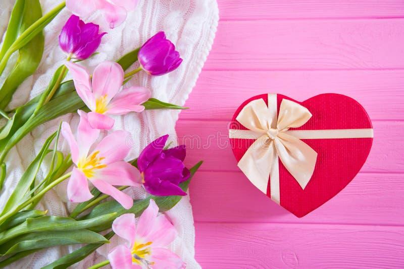 Caixa de presente vermelha na forma do coração e do ramalhete macio de tulipas bonitas no fundo de madeira cor-de-rosa foto de stock