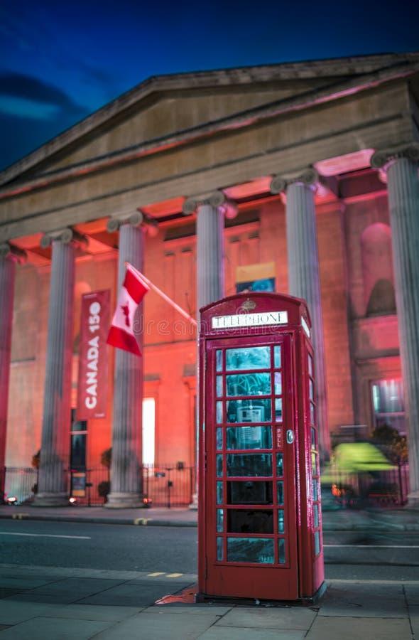 Caixa de telefone e casa vermelhas de Canadá na noite fotos de stock