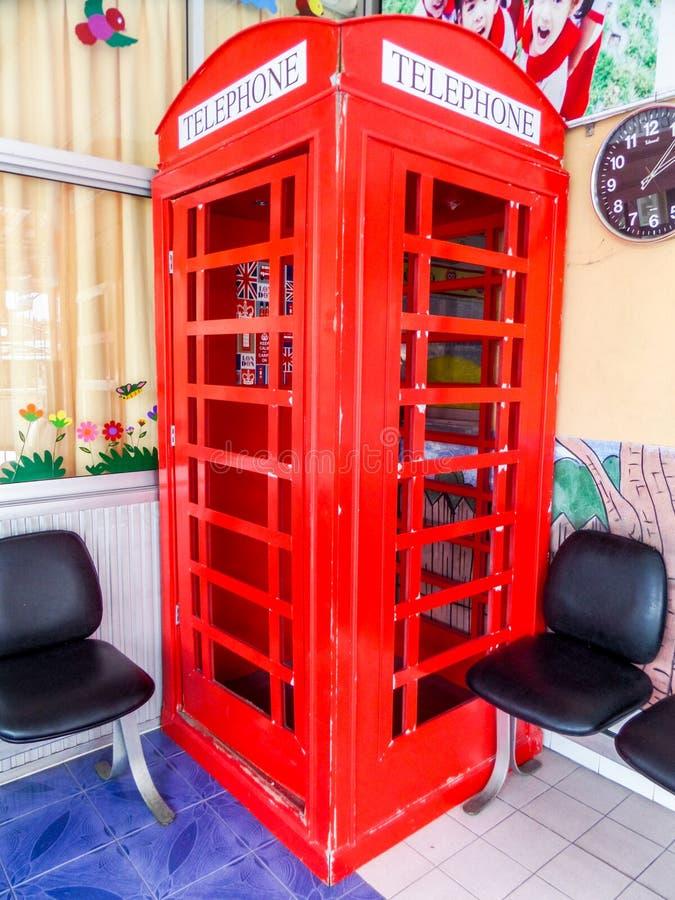 Caixa de telefone vermelha no campo de jogos na escola fotos de stock