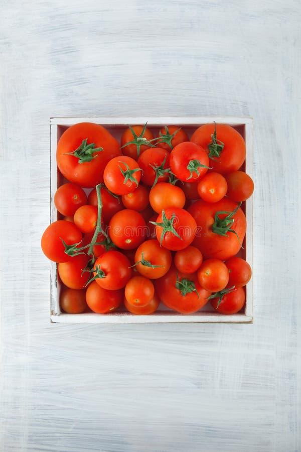 Caixa de tomates vermelhos maduros frescos em tamanhos diferentes na mesa de cozinha de madeira branca imagens de stock royalty free