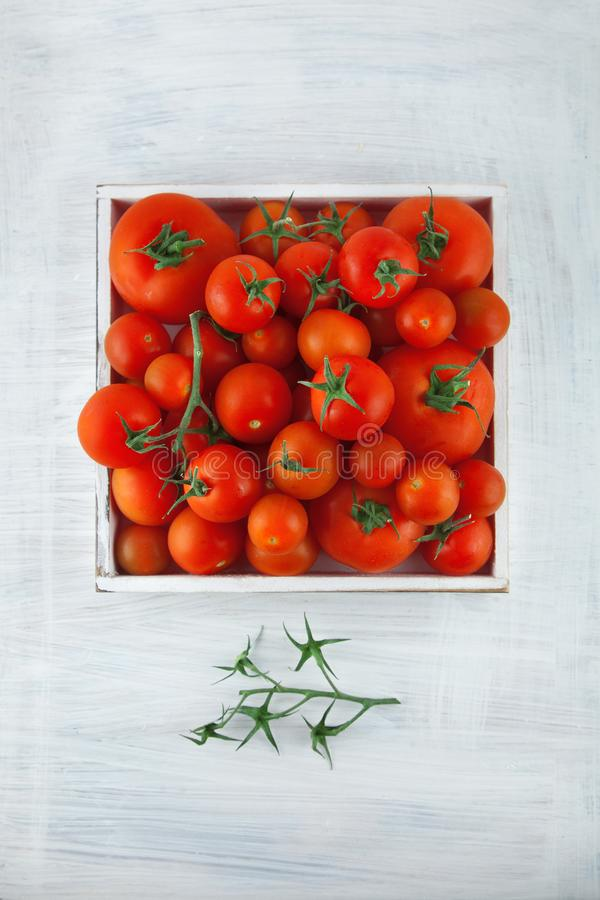 Caixa de tomates vermelhos maduros frescos em tamanhos diferentes na mesa de cozinha de madeira branca fotografia de stock