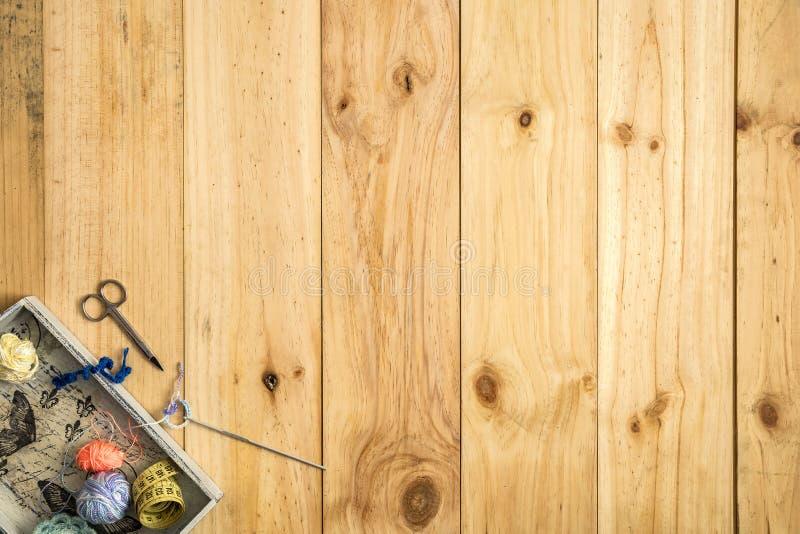 A caixa do alfaiate, linhas scissor, de fita métrica e de costura com as bobinas coloridas para retalhos no fundo de madeira foto de stock
