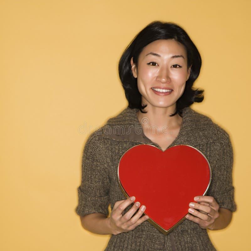 Caixa do coração da terra arrendada da mulher. foto de stock royalty free