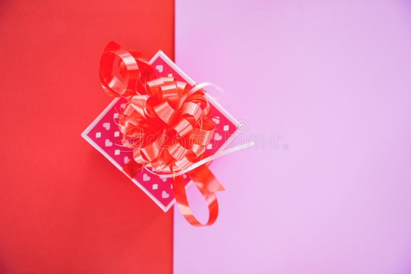 Caixa do espaço da cópia da opinião superior do rosa da caixa de presente/a atual com curva vermelha da fita para o presente ao f foto de stock