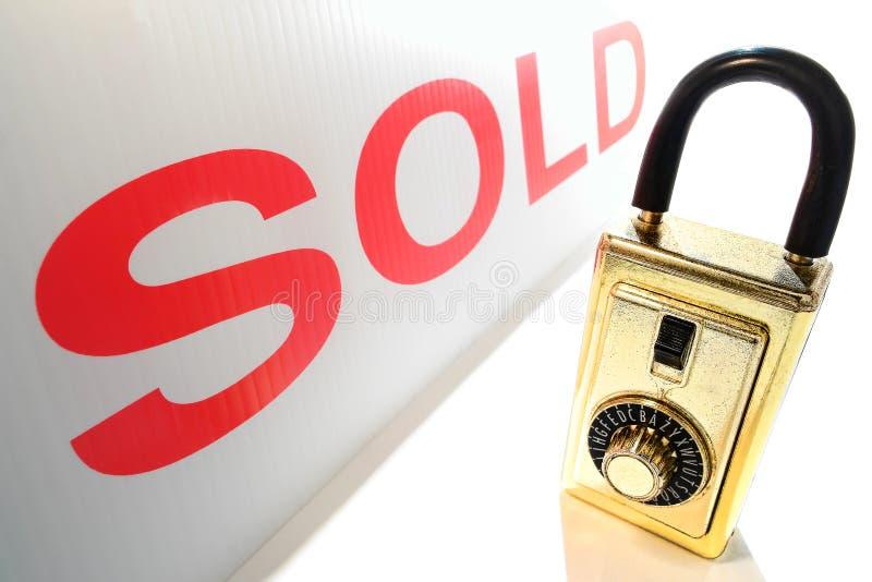 Caixa do fechamento da chave do corretor de imóveis dos bens imobiliários e sinal vendido vermelho fotografia de stock