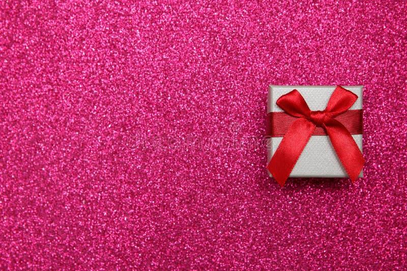 Caixa do rosa do presente no fundo cor-de-rosa de brilho o conceito do presente das felicitações Vista superior, espaço da cópia imagem de stock
