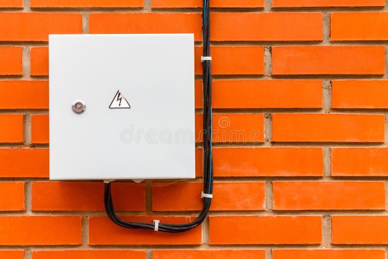 A caixa elétrica com cabo e o perigo assinam em uma parede de tijolo vermelho imagens de stock royalty free