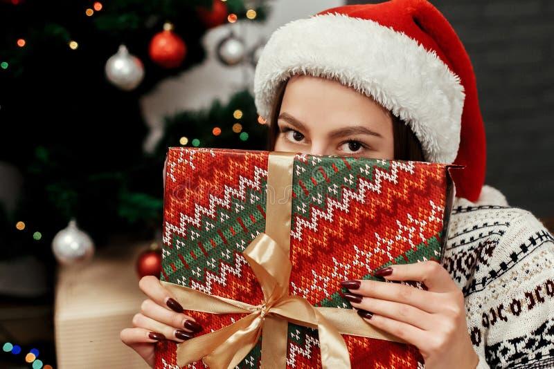 Caixa escondendo do presente de Natal da mulher feliz Ideias do presente menina no interruptor fotografia de stock royalty free