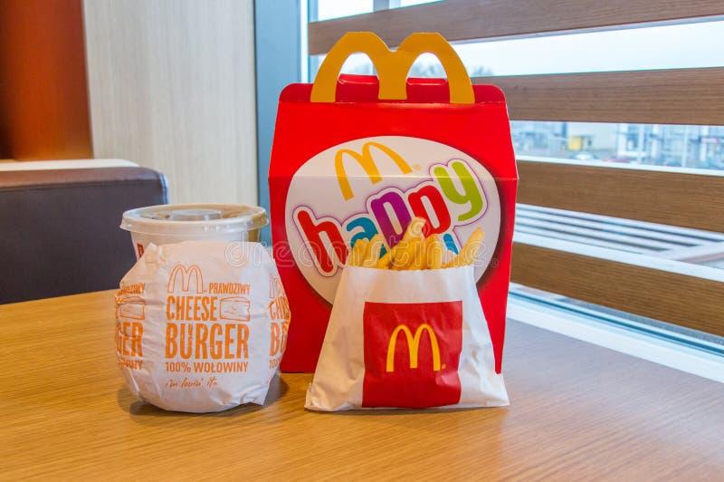 Caixa feliz da refeição de Mcdonalds com Coca-Cola, batatas fritas e cheeseburger na tabela de madeira imagens de stock royalty free