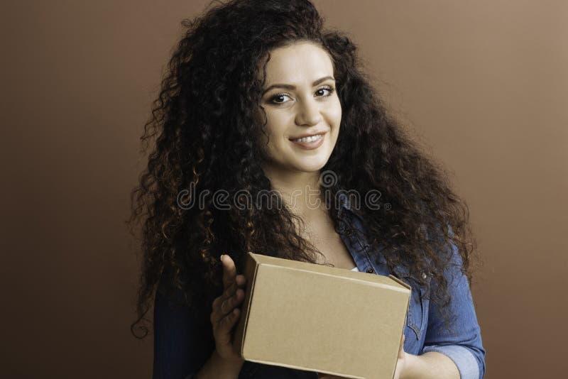 Caixa guardando fêmea deleitada em ambas as mãos fotografia de stock royalty free