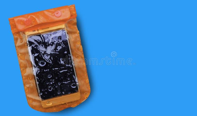 Caixa impermeável alaranjada do telefone celular com as gotas de água isoladas no fundo azul Saco do fechamento do fecho de corre imagem de stock royalty free