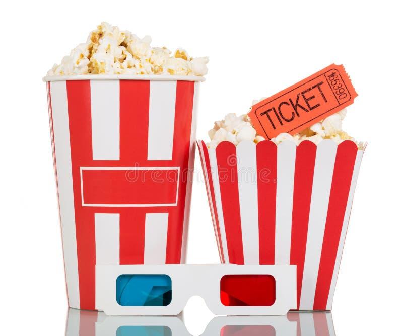 Caixa listrada completa com a pipoca, o bilhete do filme e os vidros 3D isolados em um branco imagens de stock