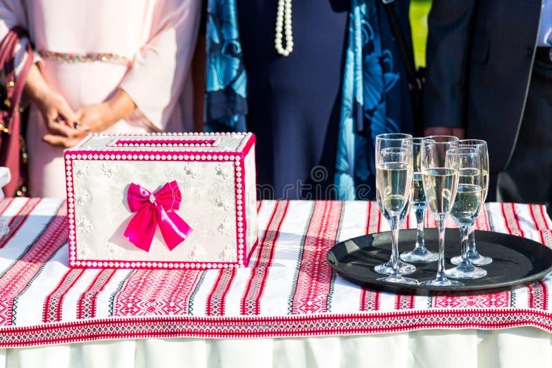 Caixa para cumprimentos de vermelho e de branco Vidros de vinho para o champanhe na tabela imagens de stock