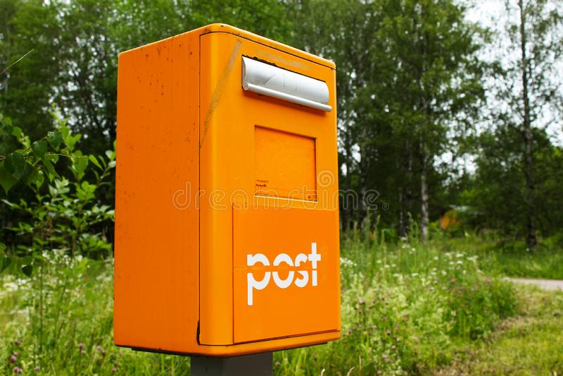 Caixa postal amarela velha no campo no fundo verde imagens de stock royalty free