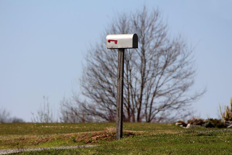 Caixa postal do metal do cinza montada no polo de madeira sobre o monte pequeno cercado com grama e a grande árvore no fundo clar foto de stock