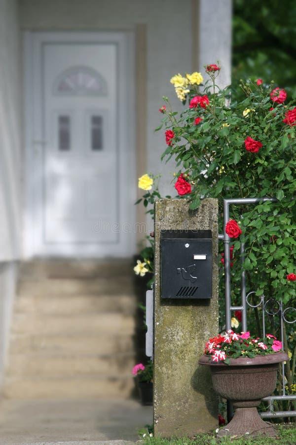 Caixa postal e flores na frente de uma casa foto de stock royalty free
