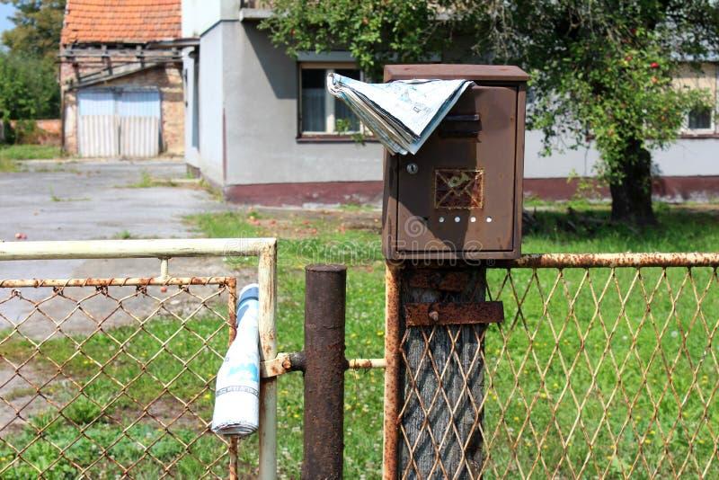Caixa postal quebrada oxidada com o jornal desvanecido montado no polo de madeira atrás da cerca de fio com a casa abandonada da  foto de stock
