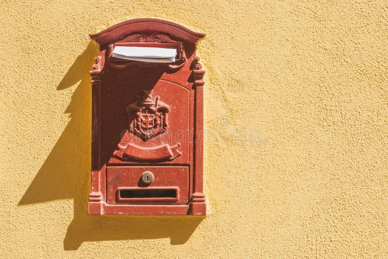 Caixa postal vermelha com letra na parede amarela imagem de stock