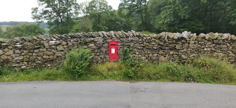 Caixa postal vermelha na parede de Drystone imagem de stock royalty free
