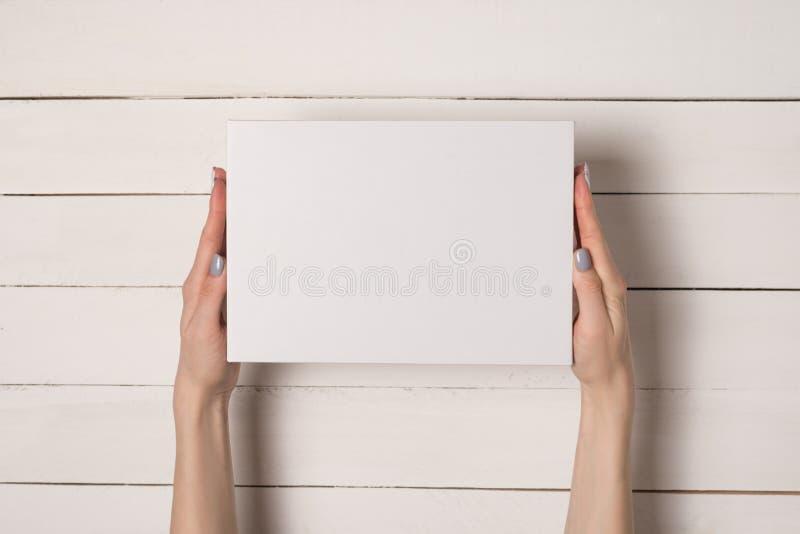 Caixa retangular branca nas m?os f?meas Vista superior Tabela branca no fundo foto de stock