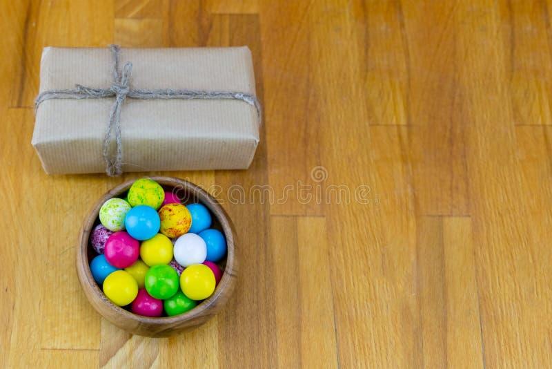 Caixa retangular festiva da base no papel de embalagem marrom com corda natural e na bacia de drageias dos doces em um fundo de m imagens de stock