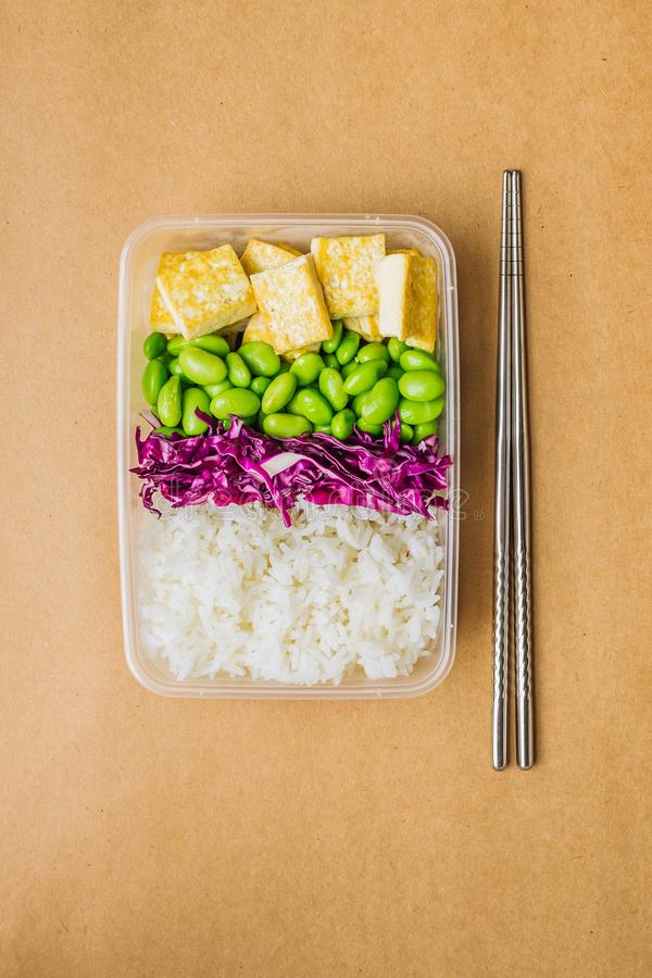 Caixa saudável do bento do vegetariano do asiático-estilo com arroz, tofu fritado, feijões do edamame e couve vermelha e hashis d fotografia de stock royalty free