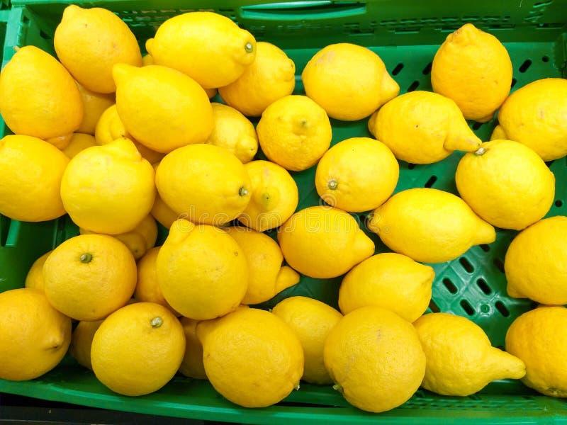a caixa verde plástica na abundância do mercado de limões amarelos do montão apronta-se para ser vendida aos clientes fotos de stock royalty free