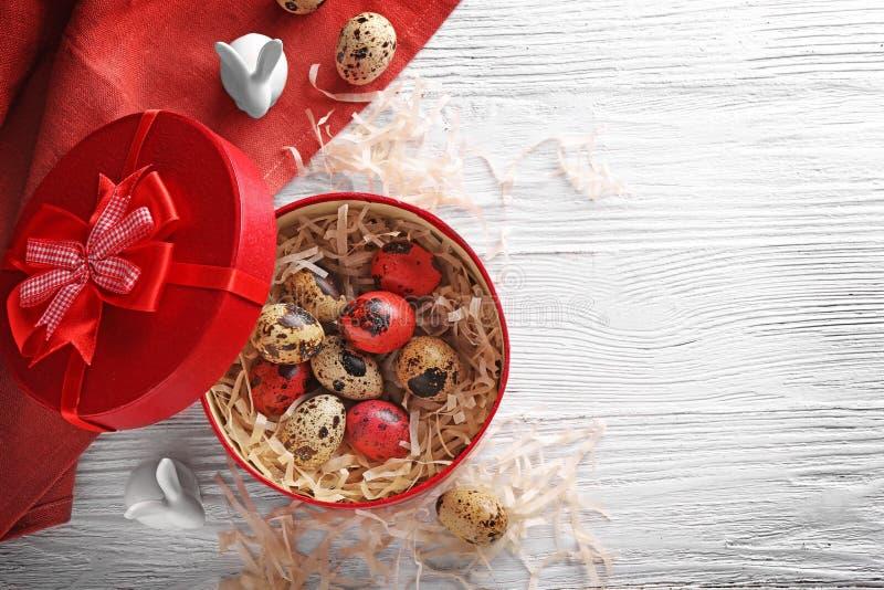 Caixa vermelha com ovos da páscoa e coelhos fotos de stock