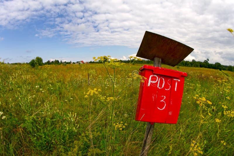 Caixa vermelha do cargo do correio em um campo fotografia de stock