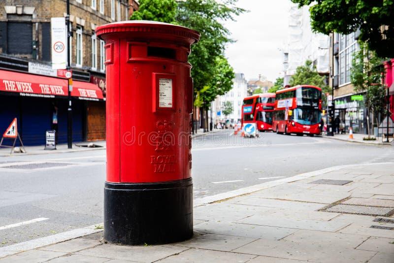 Caixa vermelha exterior do cargo da coluna de Royal Mail na rua Ônibus vermelhos do beliche no fundo fotografia de stock