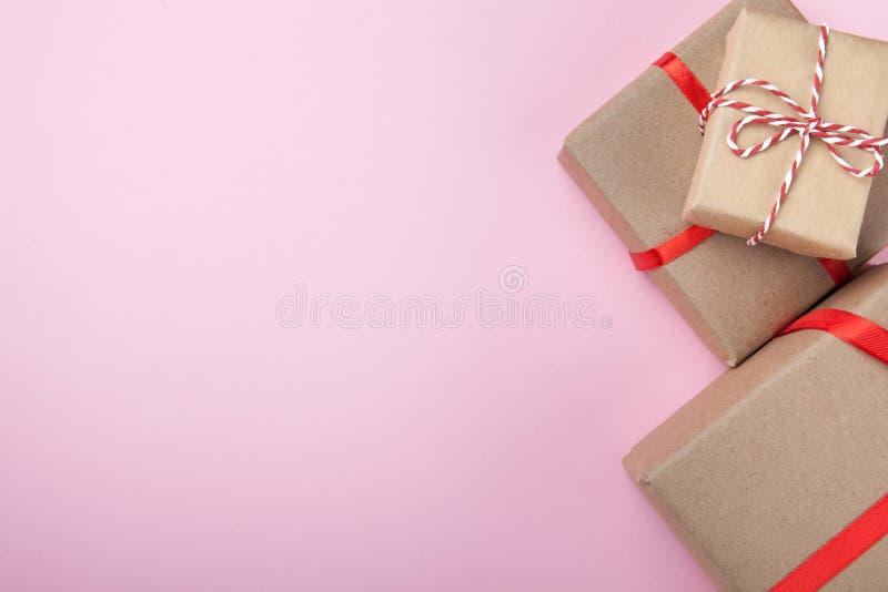Caixas atuais do papel do presente amarradas de uma corda em um fundo cor-de-rosa, vista superior Copie o espaço fotografia de stock royalty free