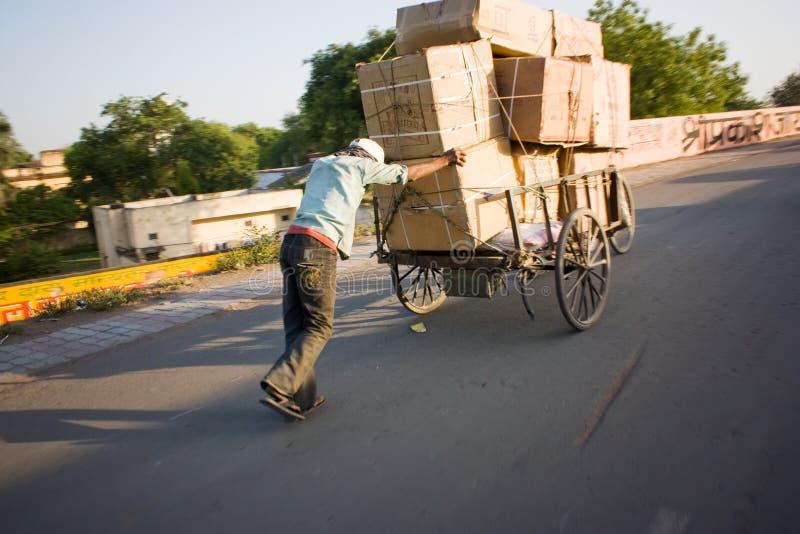 Caixas carreg do homem indiano no carro da mão imagem de stock